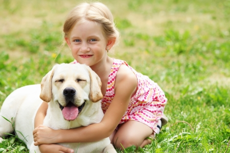 A little blond girl with her pet dog outdooors in park Stock Photo - 15597982