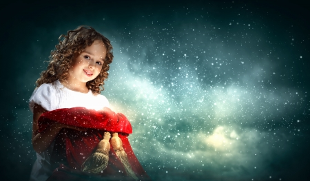 christmas magic: A cute young girl holding a christmas gift, dark background with christmas light bokeh Stock Photo