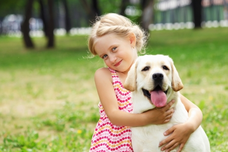 companions: A little blond girl with her pet dog outdooors in park