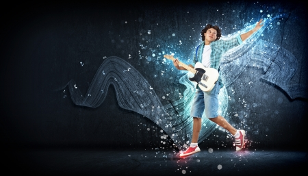 young man playing on electro guitar and jumping Stock Photo - 15597882