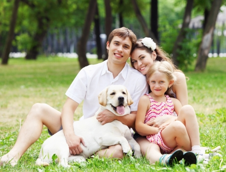 children playing outside: Young Family Outdoors in summer park with a dog