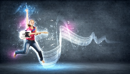 bass guitar women: young woman playing on electro guitar and jumping Stock Photo
