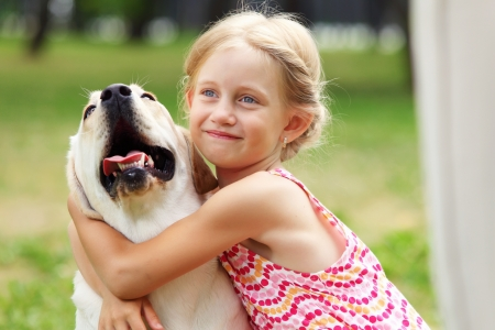 A little blond girl with her pet dog outdooors in park photo