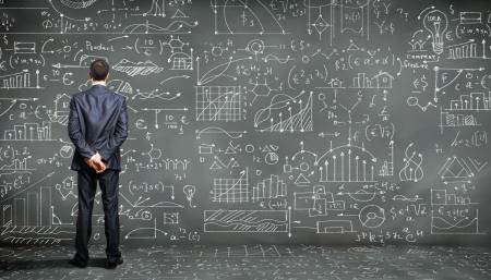 salle de classe: Homme d'affaires debout contre le tableau noir avec une grande quantit� de donn�es �crite sur elle