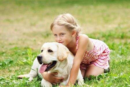 A little blond girl with her pet dog outdooors in park Stock Photo - 15597960