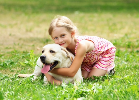 A little blond girl with her pet dog outdooors in park Stock Photo - 15597875