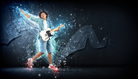a guitarist boy playing guitar: young man playing on electro guitar and jumping Stock Photo