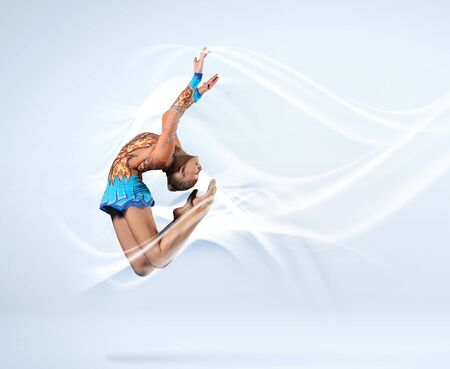 Young cute woman in gymnast suit show athletic skill on white background Stock Photo - 15647824