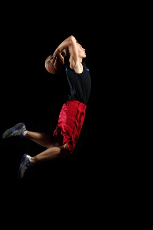 Male basketball player jumping and practicing with a ball photo
