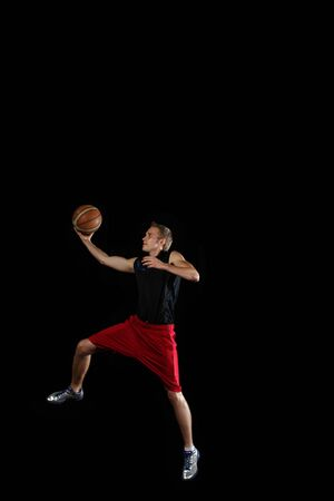 black: Male basketball player jumping and practicing with a ball
