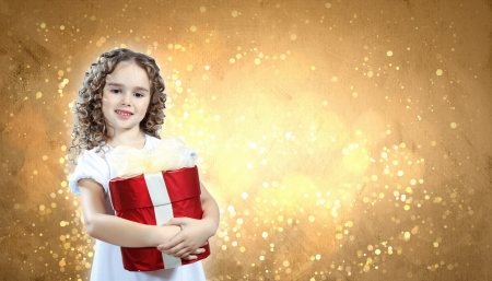 A cute young girl holding a christmas gift, dark background with christmas light bokeh Stock Photo - 15691559