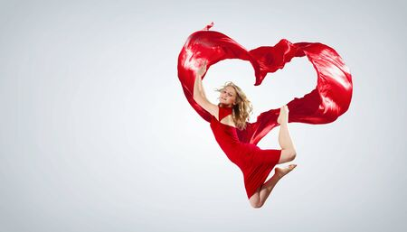 Young woman dancing with red fabric in studio and heart symbol Stock Photo - 15647808