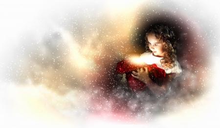 Une jeune fille mignonne tenant un cadeau de Noël, fond noir avec lumière de Noël bokeh