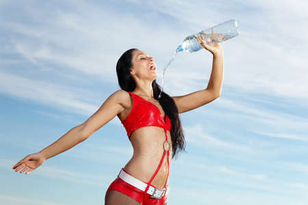 Young female sport girl in red uniform with a bottle of water Stock Photo - 15618237