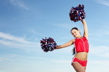 Young beautiful female cheerleader in uniform jumping high Stock Photo - 15618243