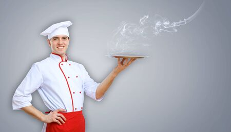 Portrait of a young male cook in red apron against colour background photo