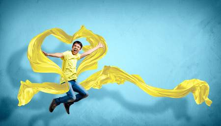 Young man dancing with yellow fabric over blue background Stock Photo - 15661700