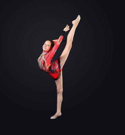 rhythmic gymnastic: Young cute woman in gymnast suit show athletic skill on black background