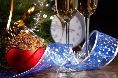 merrychristmas: New Year s still life with glasses of champagne  Decorations and ribbons on a bright color background