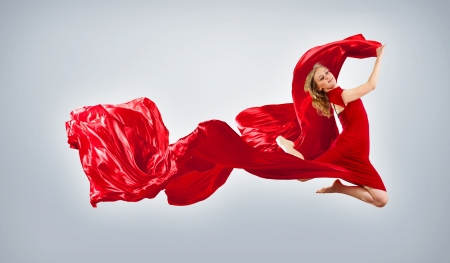 Portrait of a dancing young woman with red fabric photo
