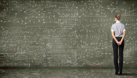 class room: Business person standing against the blackboard with a lot of data written on it