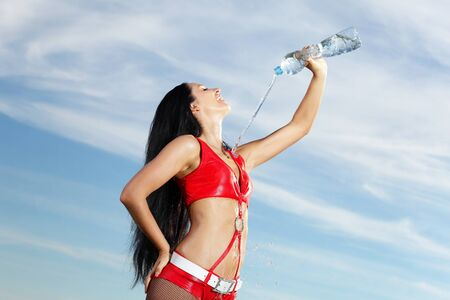 Young female sport girl in red uniform with a bottle of water photo