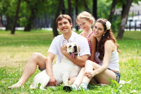 30 to 35: Young Family Outdoors in summer park with a dog