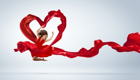 girl in red dress: Young woman dancing with red fabric in studio and heart symbol