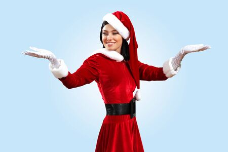 Santa Girl presenting your product, in costume and white gloves Stock Photo - 15684783