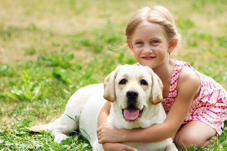 A little blond girl with her pet dog outdooors in park Stock Photo - 15683949
