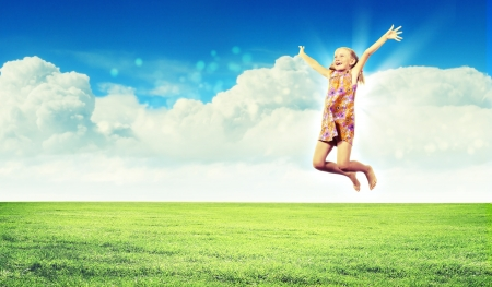 Photo of little girl jumping and raising hands against nature background photo