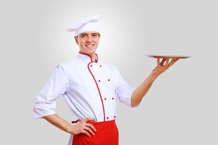 Young male chef in red apron against grey background