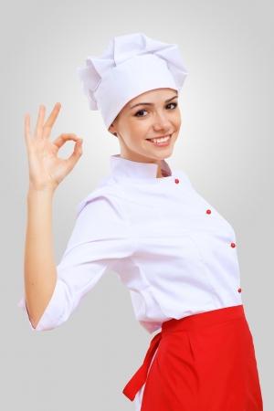 Cocinero joven mujer en delantal rojo sobre fondo gris photo