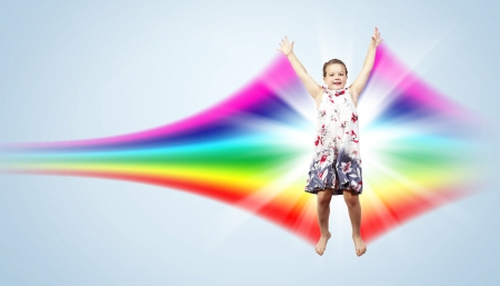 Photo of little girl jumping and raising hands against rainbow background Stock Photo - 15695949