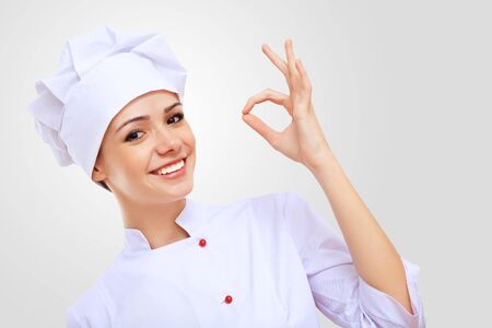 female chef: Young female chef in red apron against grey background