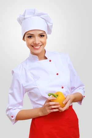 Young female chef in red apron against grey background photo