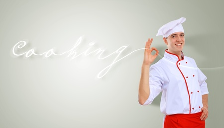 Portrait of a young male cook in red apron against colour background Stock Photo - 15695933