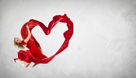 corazones azules: Baile de la mujer joven con la tela roja en el s�mbolo de estudio y el coraz�n