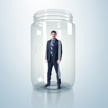 Businessman trapped inside a transparent glass jar Stock Photo - 15696714