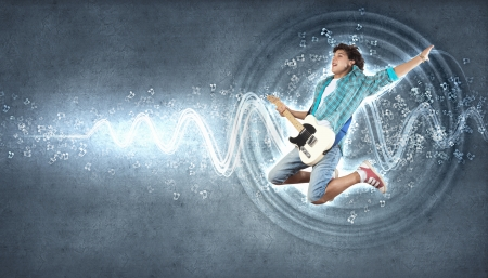 young man playing on electro guitar and jumping Stock Photo - 15696892
