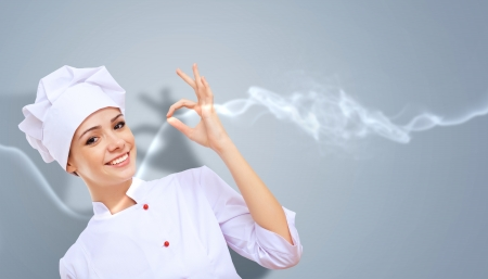 restaurant staff: Young female chef in red apron against collour background