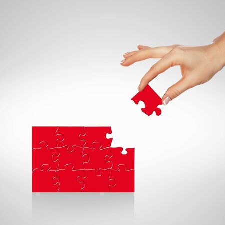 creative background: Image of colour puzzle pieces and human hand