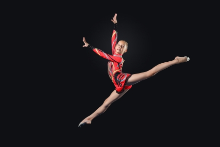 female gymnast: Young cute woman in gymnast suit show athletic skill on black background