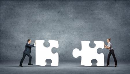 entreprise puzzle: �quipe de gens d'affaires collaborer brandissant des pi�ces de puzzle comme une solution � un probl�me