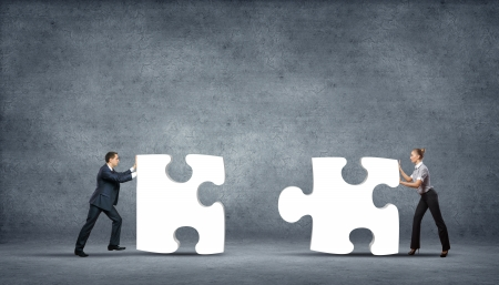 partner: Team of business people collaborate holding up jigsaw puzzle pieces as a solution to a problem