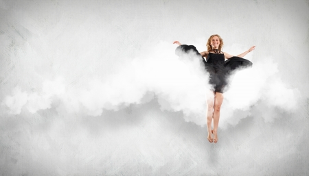 Portrait of a dancing young woman with white cloudy smoke around photo