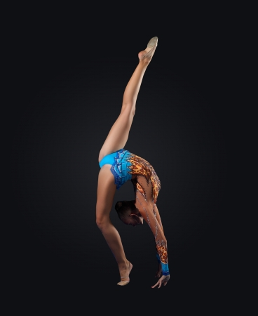 acrobat gymnast: Young cute woman in gymnast suit show athletic skill on black background