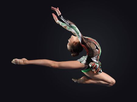 'ballet girl': Young cute woman in gymnast suit show athletic skill on black background