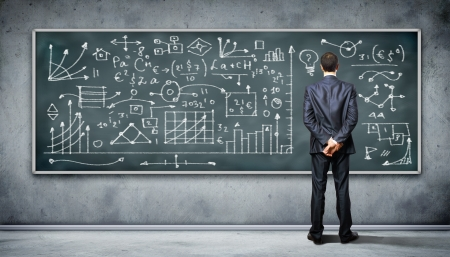auditorium: Business person standing against the blackboard with a lot of data written on it