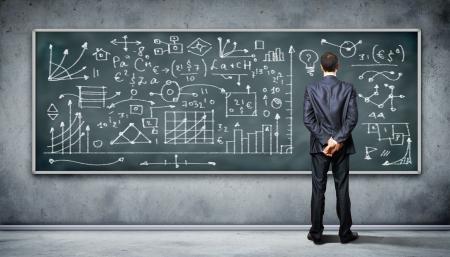 Homme d'affaires debout contre le tableau noir avec une grande quantité de données écrite sur elle Banque d'images